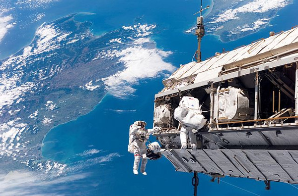 Astronauts on space walk with ocean in background